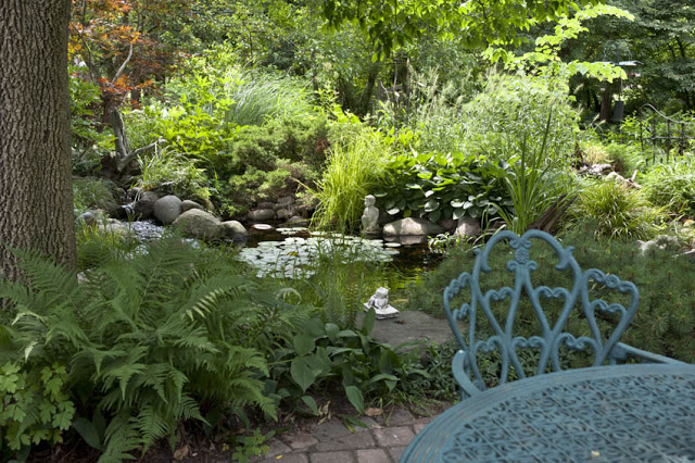 A wrought iron table and chair lends an elegant touch to a brick patio lined with frothy ferns. Sunlight dapples on the pond's surface just beyond.