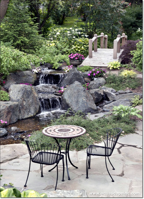 A simple patio with a bistro table creates a cozy, intimate spot for dining by the waterfalls.