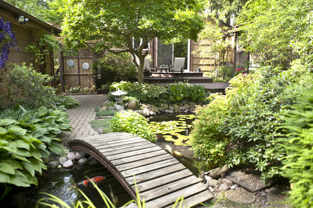 Patios, walkways, and a bridge carve a unique garden path around and over the stream and water garden.