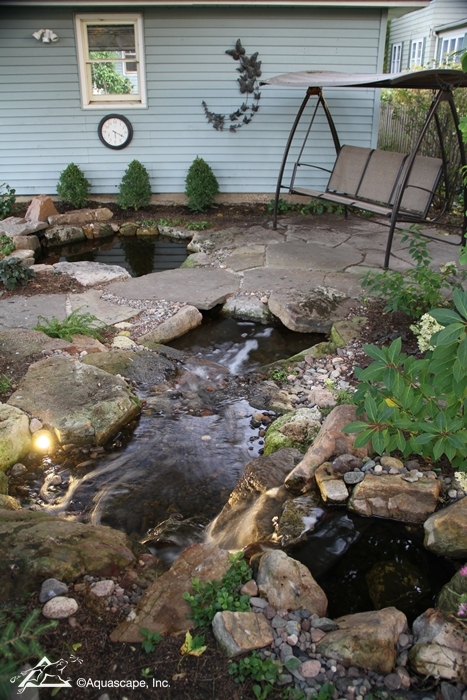 Beautiful Backyards often include a pond or water garden with a seating area.
