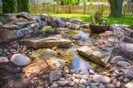 A Patio Pond with aquatic plants was cleverly added to the edge of this waterfall's stream.