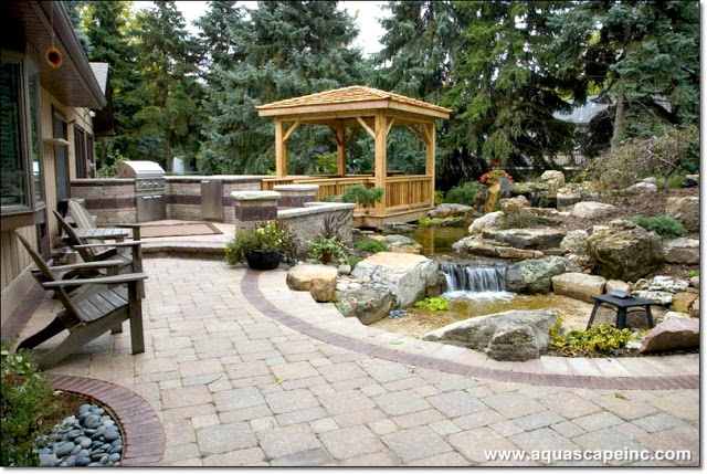 Outdoor kitchen to the left, beautiful paver patio for enjoying waterfront views, and a floating deck and gazebo for personal interaction with this amazing pond and waterfall.