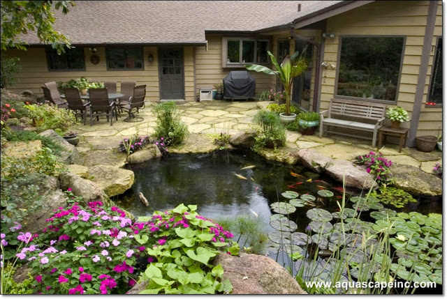 Flagstones create a natural-looking patio to complete this ecosystem pond. Note the large windows for indoor viewing!
