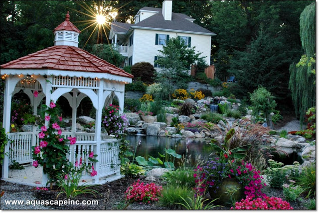 A cottage-style gazebo provides the optimal viewing vantage of this lovely pond and waterfall.