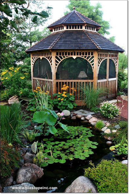 The charming gazebo provides an idyllic backdrop for a pond dotted with lily pads.