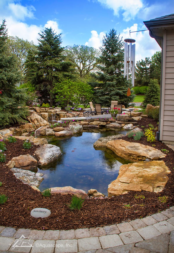 Enjoy your backyard patio with a water feature wrapping around it.