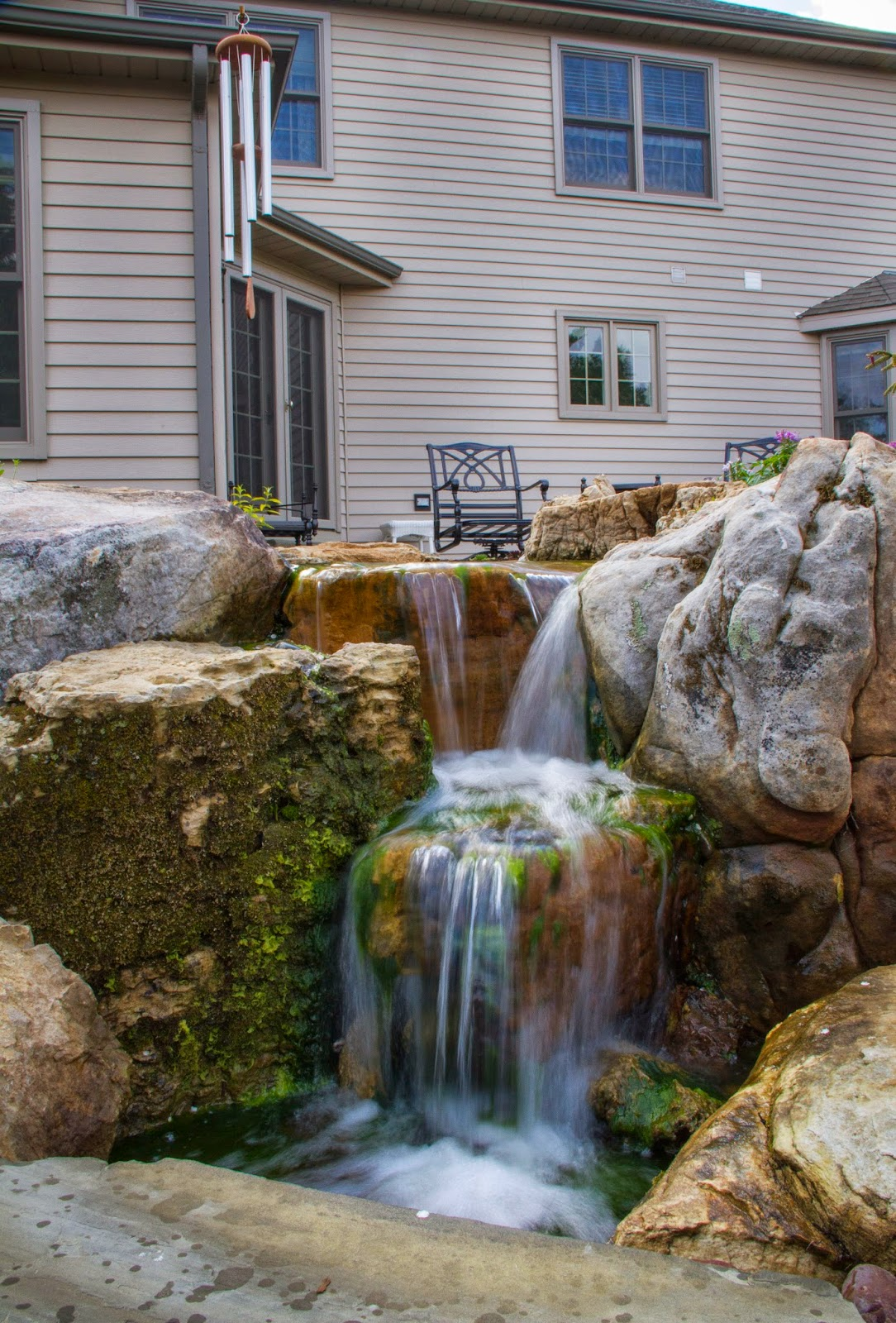 A mossy waterfall not only provides beauty but adds soothing sounds to this perfect backyard.
