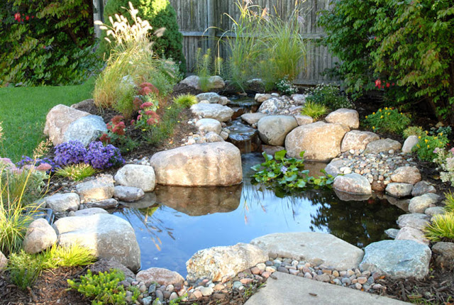 The waterfall is in proportion to this smaller pond, nestled snug against the corner of a patio.