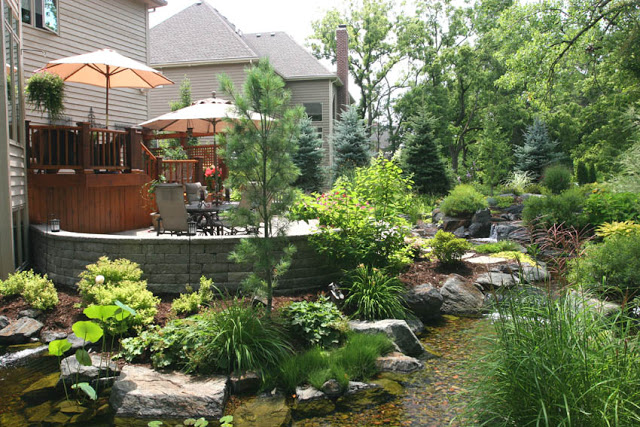 A multi-layered deck provides ample seating for festive gatherings by the waterfall and stream.
