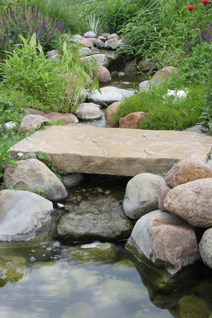 A close-up of the smaller foot bridge displays the intricate rock work that creates a babbling brook.v