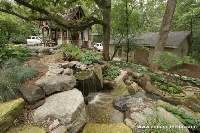 Water falls over a series of cascading rocks and gravel. Shade loving plants add softness to the cool stone of this water feature.
