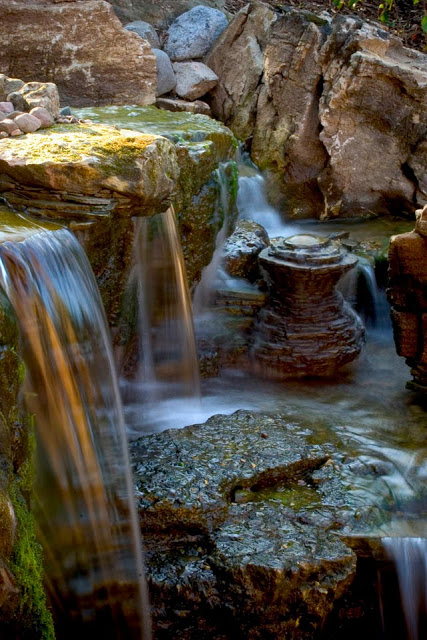By the looks of the moss and worn appearance of the rocks, you'd never know this is a new backyard waterfall.