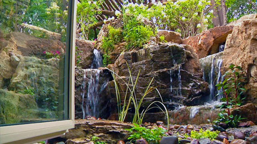 This rustic waterfall can be seen right outside the office window located in the home's lower level.