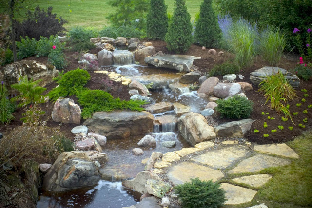 This newly created waterfall and stream was graced with a few mature plantings to tie it into its lush surroundings.
