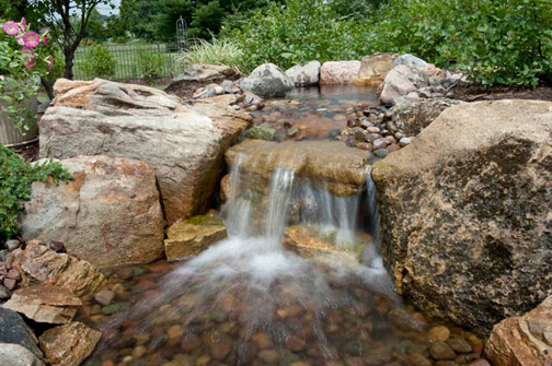 Even a small rustic waterfall such as this one can add drama and an air of rusticity to the landscape.