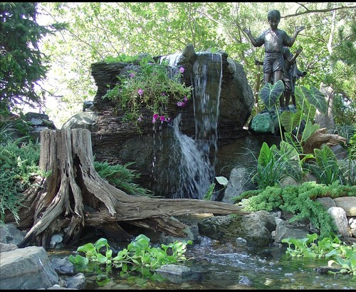 Unique use of rock, log, and statues in a backyard pond and waterfall by New Jersey Pond Contractor BJL Aquascapes